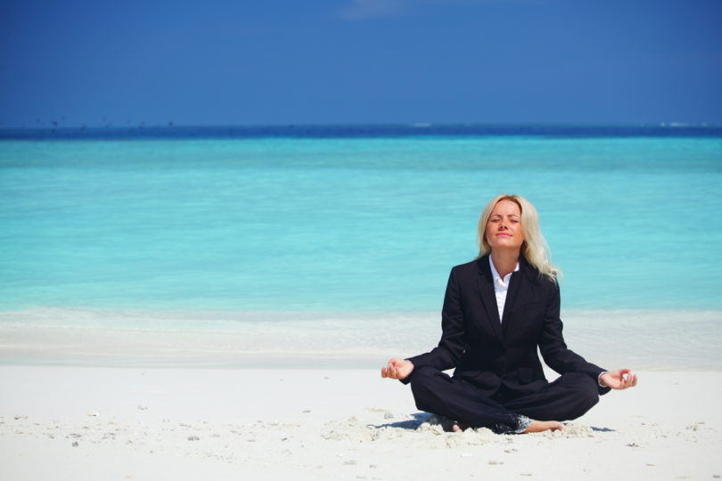 yoga business woman in lotus pose on the beach
