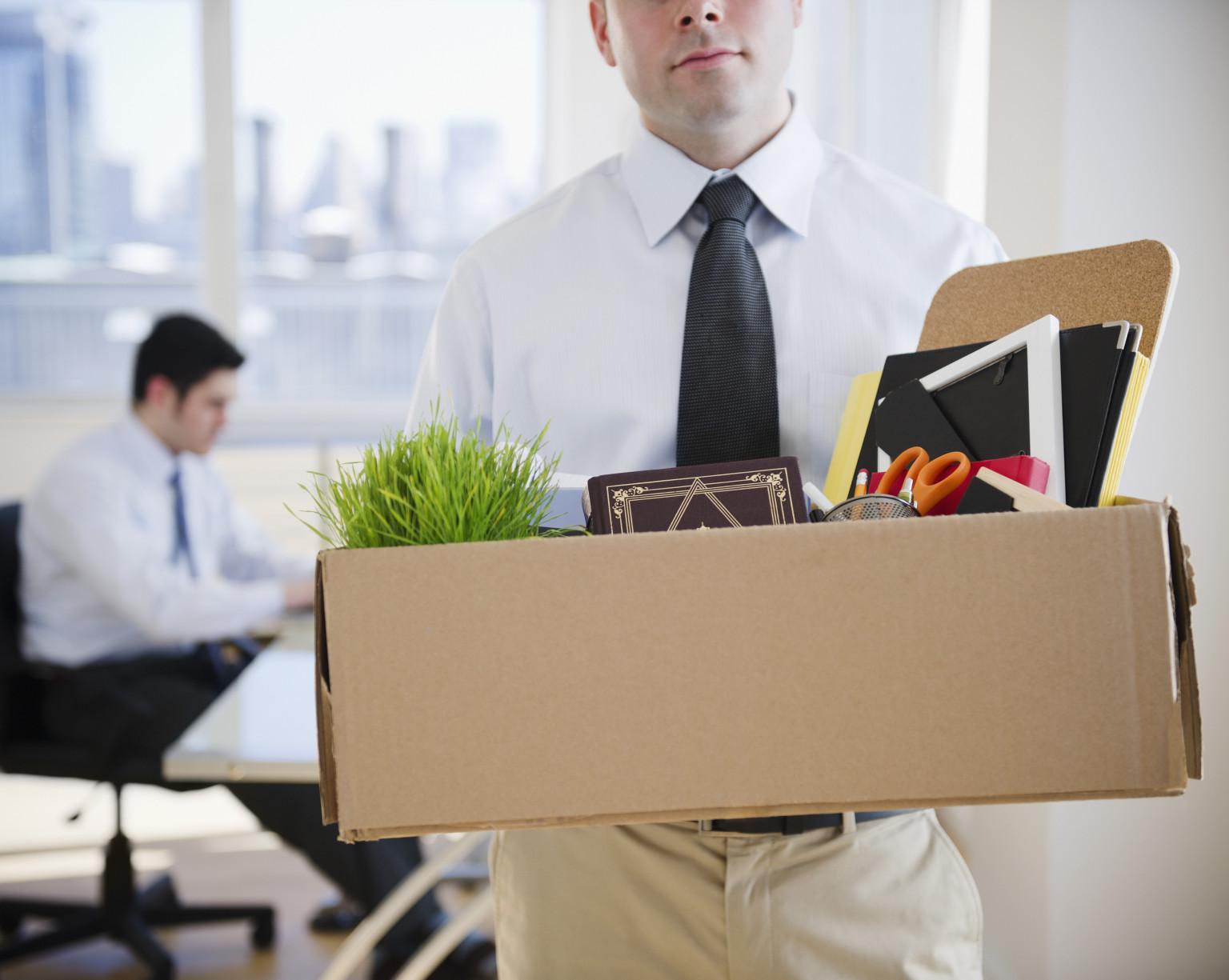 Fired Caucasian businessman carrying personal belongings