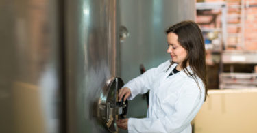 Female technologist in white overall near tub filled with olive oil in manufacturing environment