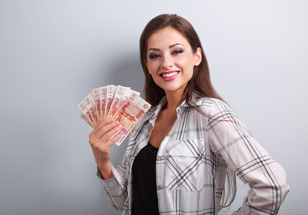 Happy young casual woman holding rubles with toothy smiling on blue background