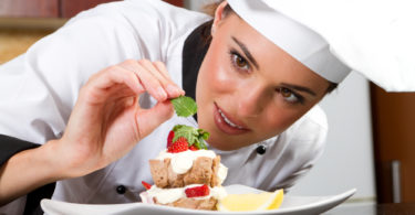 beautiful professional female chef decorating dessert
