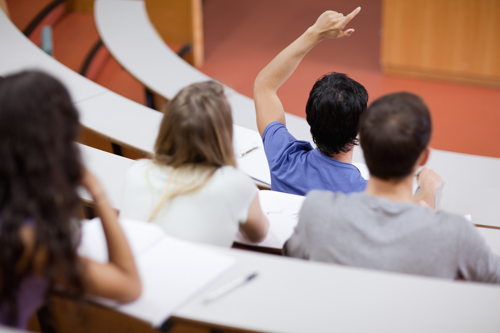 Young student raising his hand while his classmates are taking notes in an amphithater