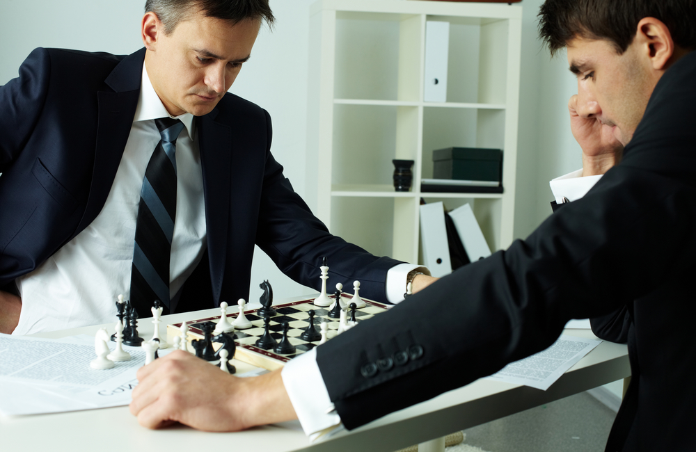 Image of two businessmen looking at chessboard while playing chess