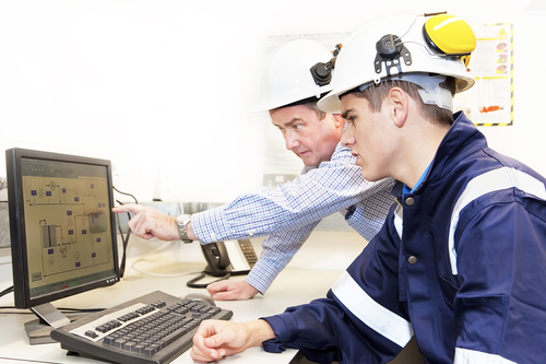 Senior and junior engineers discussing work together in office, senior man pointing at screen