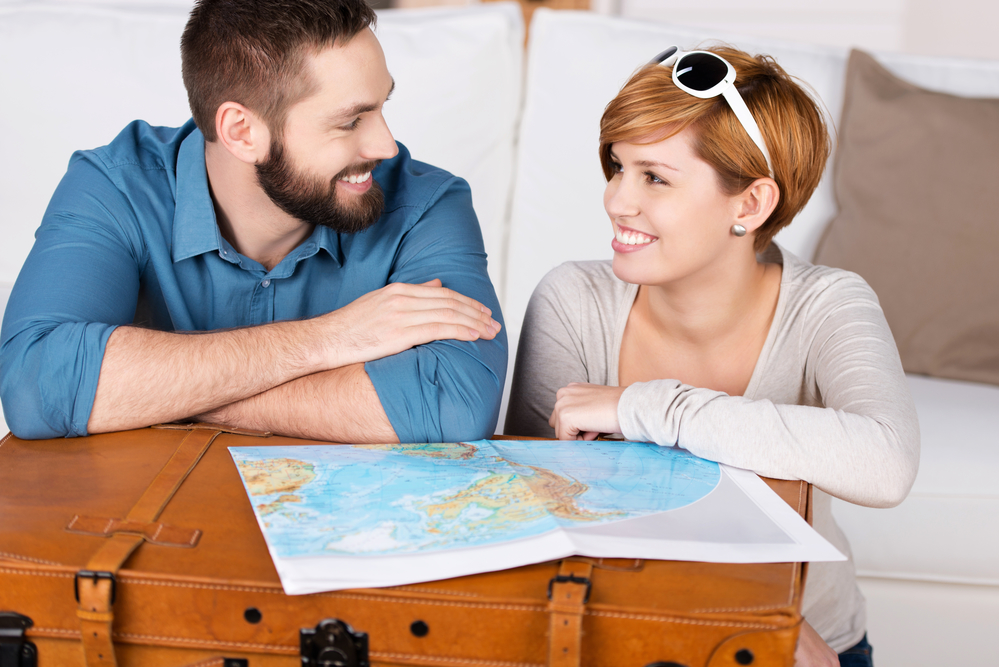 Young happy couple planning a travel with map
