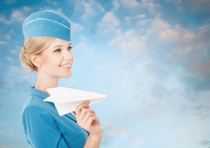 Charming Stewardess Holding Paper Plane In Hand. Blue Sky Background.