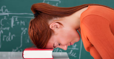 Side view of sad young female student leaning head on book in classroom