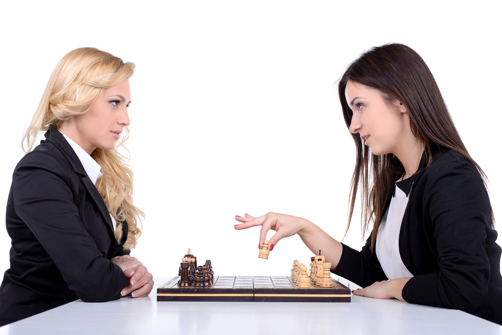 Young business women playing chess isolated on white background