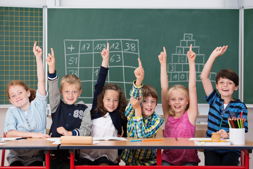Enthusiastic group of young kids in class sitting in a row at their desk raising their hands in the air to show the know the answer to a question