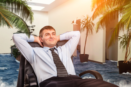 Businessman is dreaming about vacations in his office