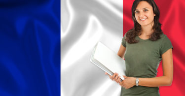 Smiling young female student  over French flag
