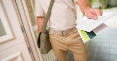 Postman delivering a letter outside a home