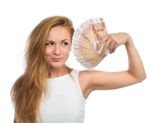 Happy young woman holding up many cash money five thousand russian rubles notes in hand looking at the camera isolated on a white background