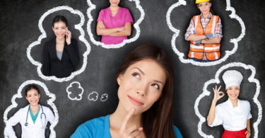 Career choice options - student thinking of future education. Young Asian woman contemplating career options smiling looking up at thought bubbles on a blackboard with images of different professions