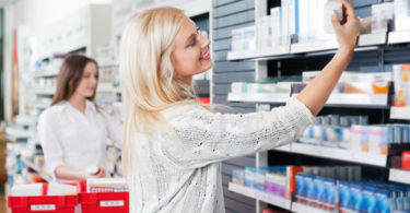 Happy woman buying medicine at pharmacy store