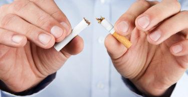 Human hands breaking up cigarette