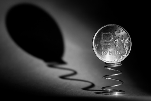 Coin one ruble on the spring casts a shadow in the form of a balloon. Black and white photo closeup