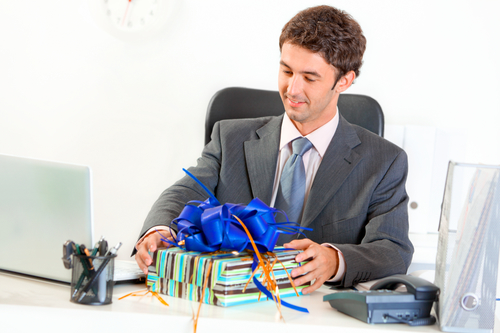Pleased modern businessman sitting at office desk and looking on gift