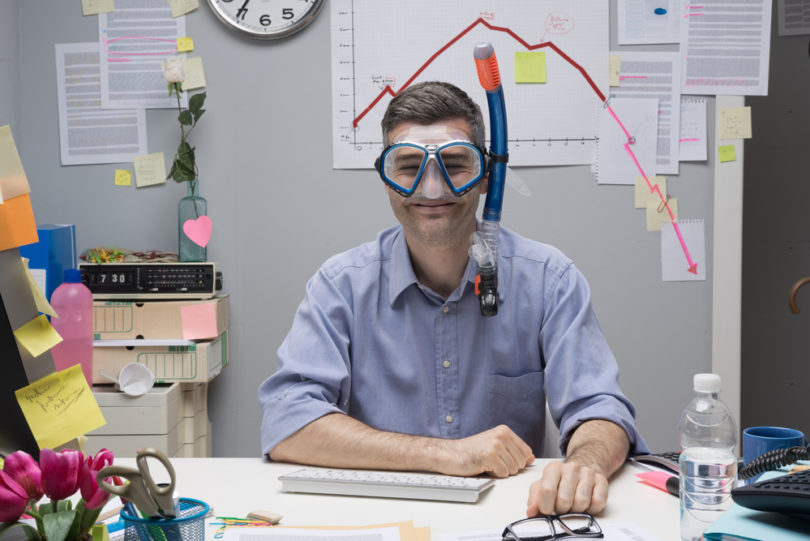 Smiling office worker wearing scuba mask with negative business chart on background.