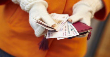 Woman hands holding purse with Russian roubles, financial crisis in Russia concept
