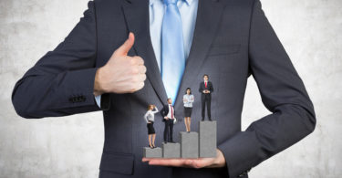 A man holding a pedestal in the shape of a bar chart, four businesspeople standing on it. Front view, no head. Concrete background. Concept of career growth.