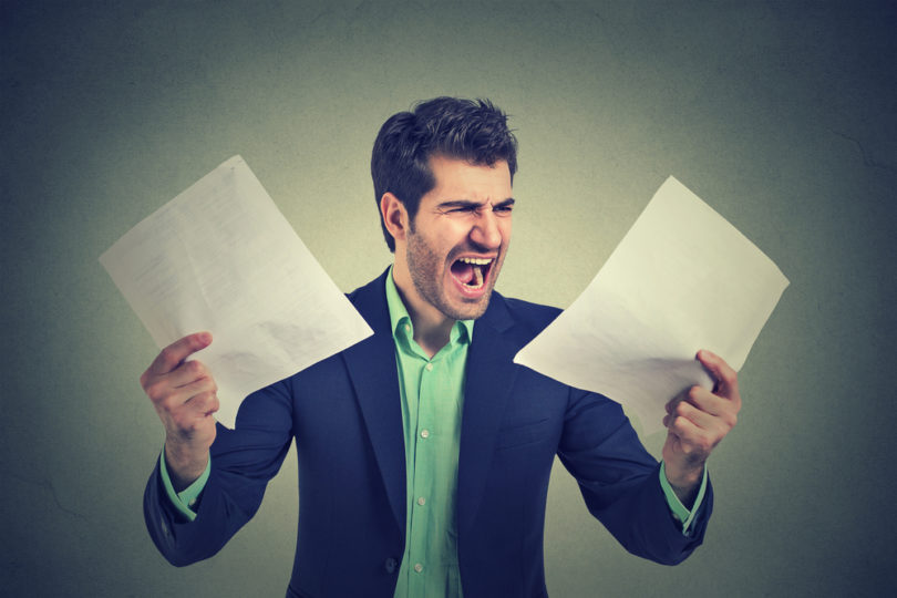 Angry stressed screaming business man with documents papers paperwork isolated on gray office wall background. Negative emotions face expression