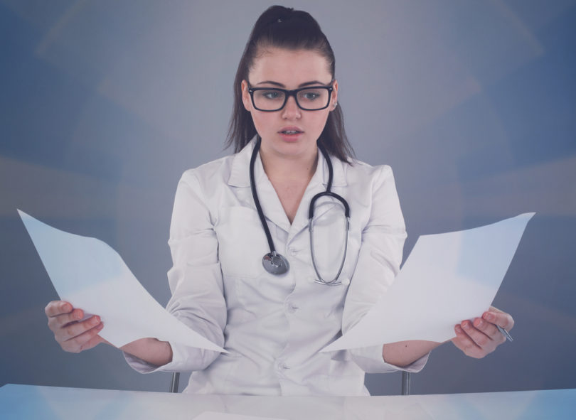 Nurse in white robe and black glasses is writing her report and thinking about it at the  table against of grey background