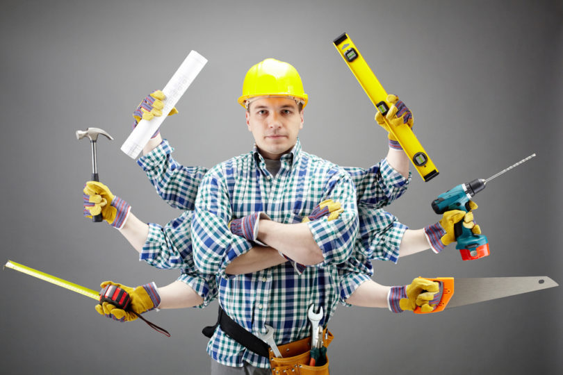 Portrait of serious craftsman with different tools in six hands