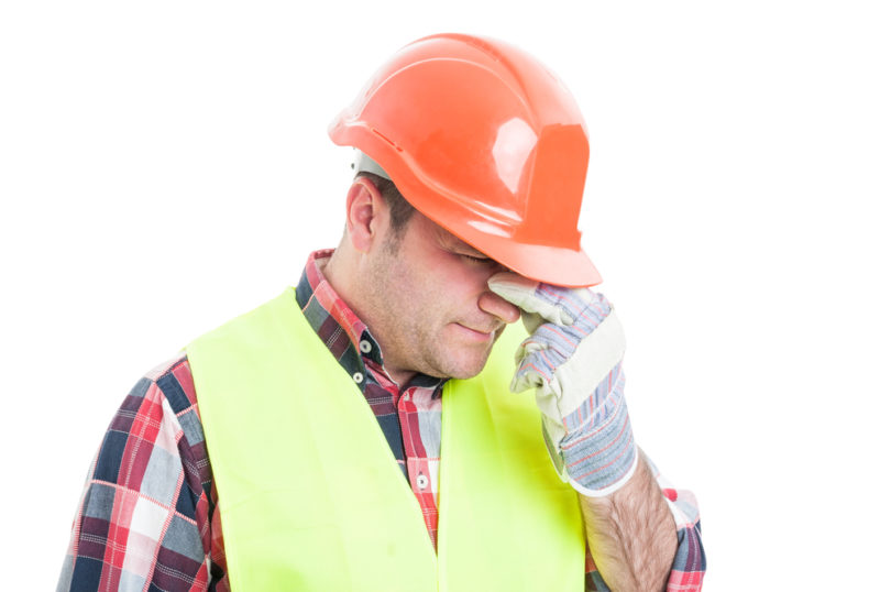 Portrait of stressed male builder looking upset and having problems isolated on white background
