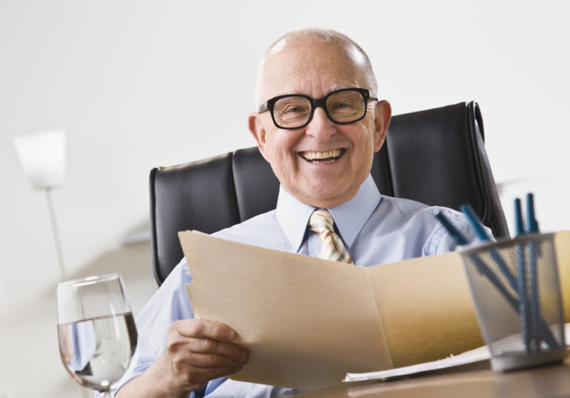 An elderly business man seated in an office and smiling.  He is holding a file folder and is wearing glasses.  Horizontally framed shot.
