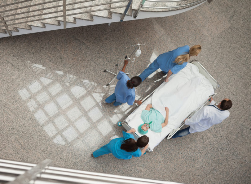 Three nurses and one doctor pushing a patient in a gurney in hospital corridor