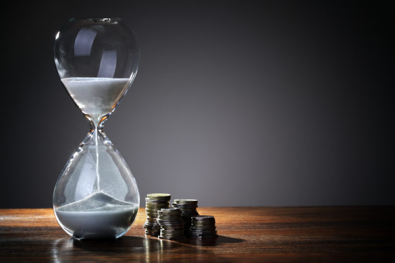 Deadline and time is money concept with hourglass and British coin currency