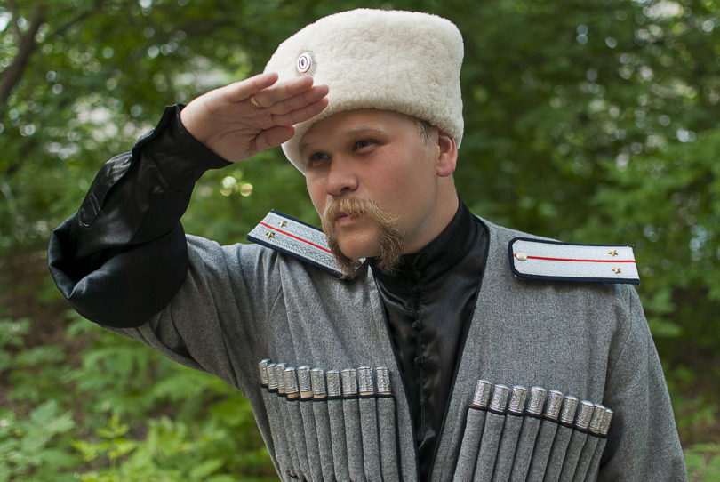 Young man in a cossack clothes in a forest