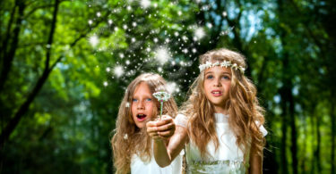 Fantasy portrait of cute girls with magic wand in forest.