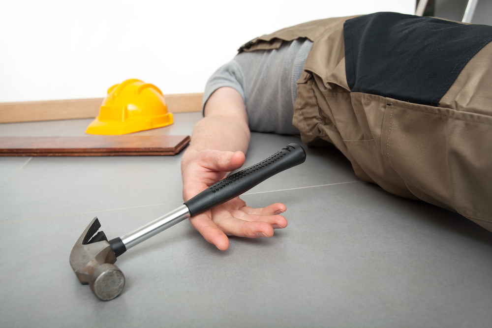 Unconscious worker lying on the floor with hammer in the hand