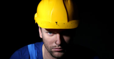 Portrait of young worker on dark background