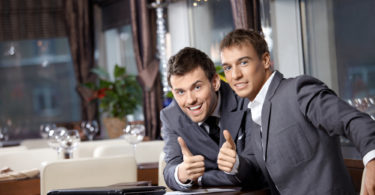 Two joyful businessmen at restaurant celebrate the transaction