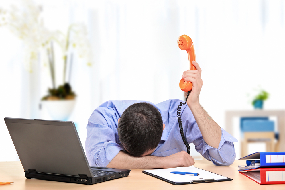An exhausted businessman holding a telephone in his office
