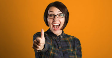 Cheerful young woman showing thumb up sign on orange background