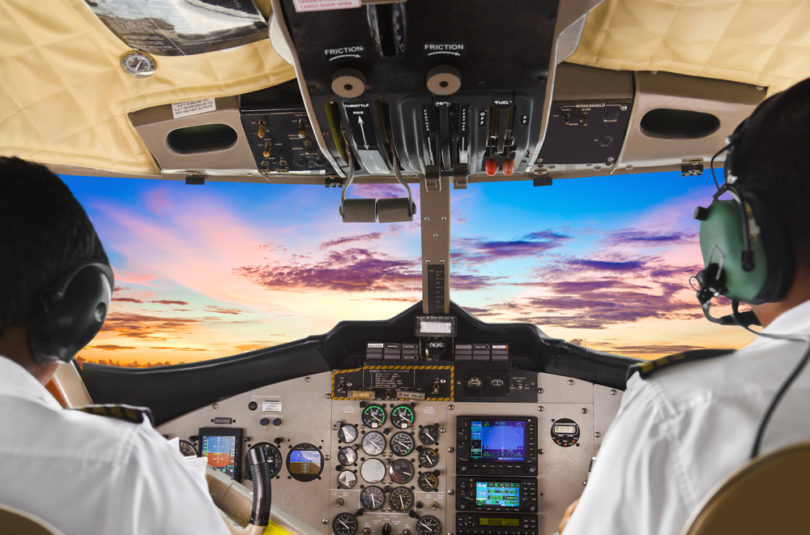 Two pilots in the plane cockpit and sunset
