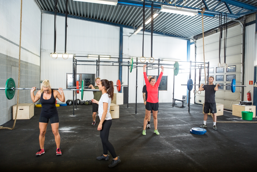 Female cross trainer assisting athletes in lifting barbells at gym