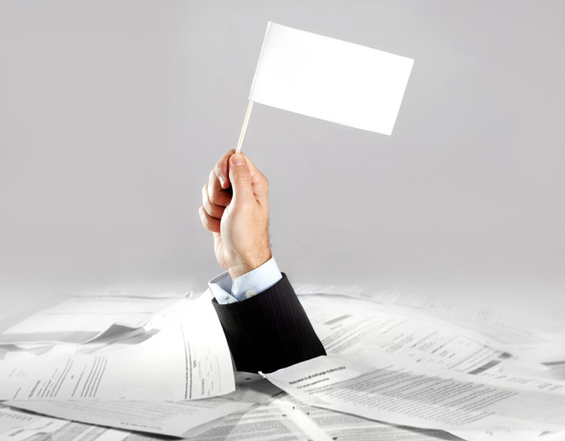 Hand of caucasian businessman emerging from office desk loaded of paperwork , invoices and a lot of papers and documents holding white flag  overworked in giving up concept