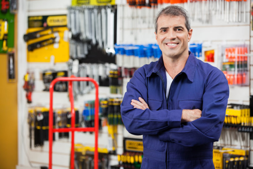 Portrait of confident worker with arms crossed standing in hardware shop