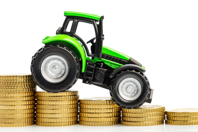 farmers in agriculture have to reckon with rising costs. higher preies in feed, fertilizer and plants. tractor with coins