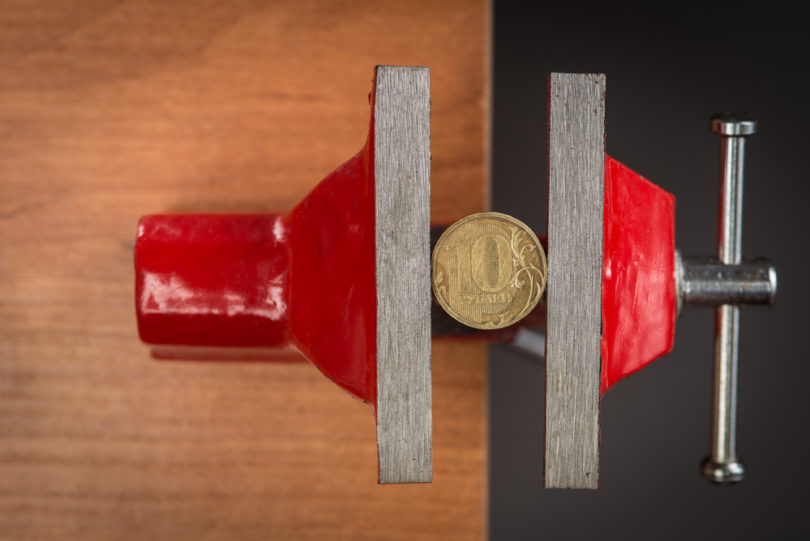 A ten rubles coin squeezed tightly in a vise tool, concept of devaluation and financial crisis.