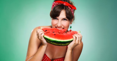 young, happy girl eating watermelon, isolated green background.