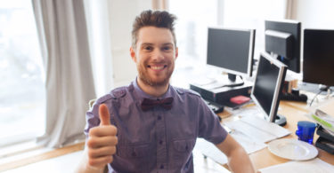 business, startup, gesture and people concept - happy businessman or creative male office worker with computers showing thumbs up