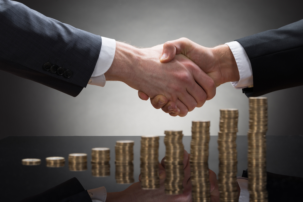 Close-up Of Two Businessmen Shaking Hands With Stack Of Coins