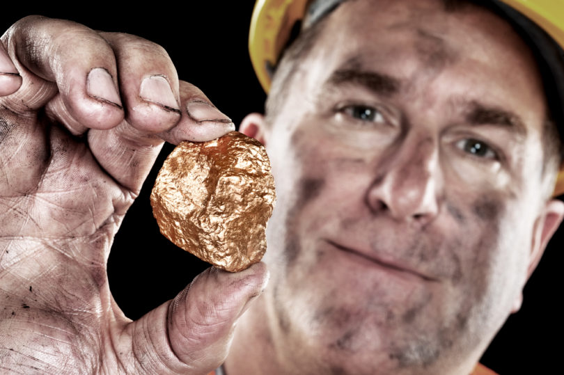 A gold miner shows a golden nugget freshly excavated from a mine.