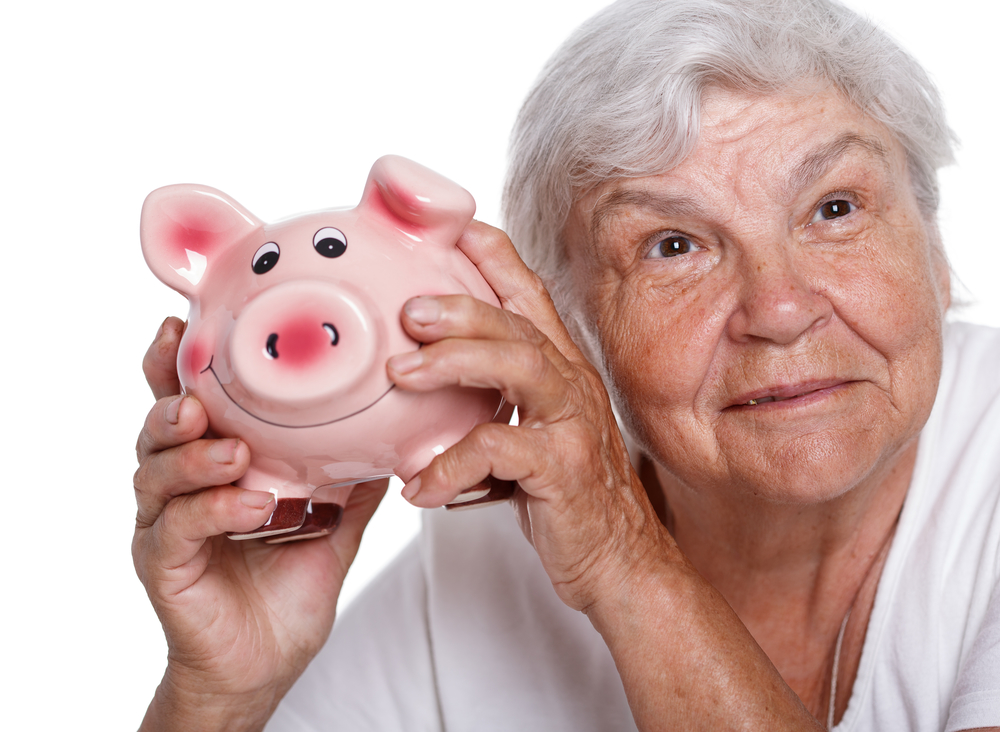 Elder woman shaking funny piggybank and listening sound of inside detecting amount. Budgeting expenses concept. Making savings and effective investment concept. Future needs deposit. Retirement wages